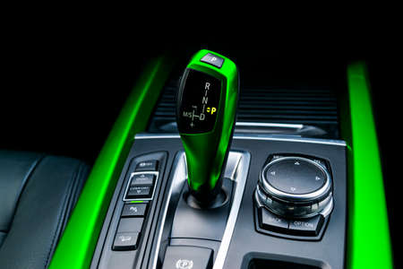 Green Automatic gear stick of a modern car. Maodern car interior details. Close up view. Car detailing. Automatic transmission lever shift. Black leather interior with stitching.