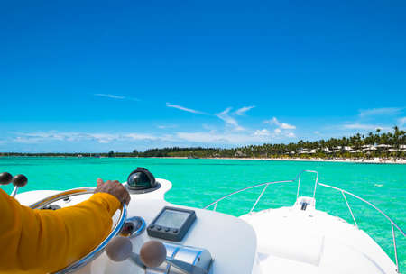 Hand of captain on steering wheel of motor boat in the blue ocean during the fishery day. Success fishing concept. Ocean yacht Archivio Fotografico
