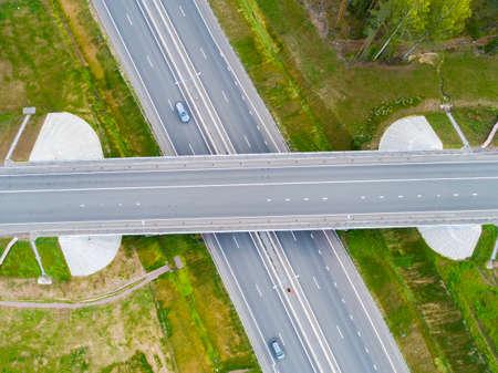 Luchtfoto van snelweg in de stad. Auto's die het viaduct oversteken. Snelwegknooppunt met verkeer. Luchtfoto vogelvlucht van snelweg. Expressway. Kruispunten. Auto passeert. Bovenaanzicht van bovenaf.