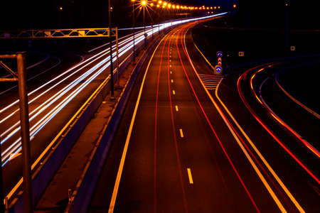 Cars light trails on a curved highway at night. Night traffic trails. Motion blur. Night city road with traffic headlight motion. Cityscape. Light up road by vehicle motion blur. Stock Photo