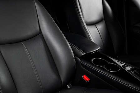 Moderne Luxusauto schwarze Lederausstattung. Teil der Lederautositzdetails mit Nähten. Innenraum des Prestige modernen Autos. Bequeme perforierte Ledersitze. Schwarzes perforiertes Leder. Professionelle Autopflege