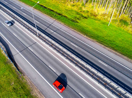 Aerial view of highway in city. Cars crossing interchange overpass. Highway interchange with traffic. Aerial birds eye photo of highway. Expressway. Road junctions. Car passing. Top view from above. Cars in motion