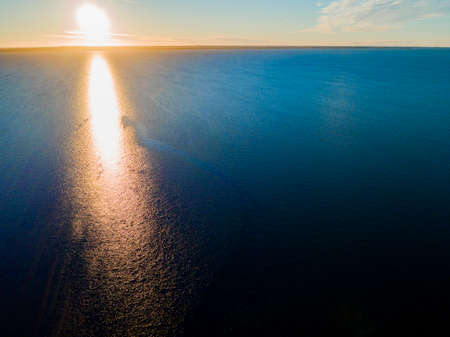 Aerial view of a Sunset sky background. Aerial Dramatic gold sunset sky with evening sky clouds over the sea. Stunning sky clouds in the sunset. Sky landscape. Aerial photography.