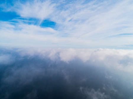Aerial view White clouds in blue sky. Top view. View from drone. Aerial birds eye view. Aerial top view cloudscape. Texture of clouds. View from above. Sunrise over the sea Stock Photo