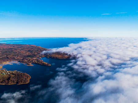 Aerial view over forest during vibrant autumn colors. Aerial view of seashore and clouds. Coastline with sand and water. Aerial drone view of forest. Aerial top view cloudscape. Texture of clouds. Stock Photo