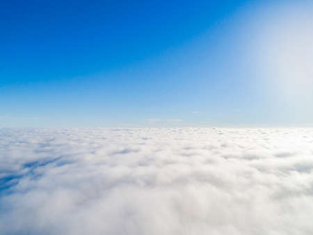 Aerial view White clouds in blue sky. Top view. View from drone. Aerial birds eye view. Aerial top view cloudscape. Texture of clouds. View from above. Sunrise over clouds Stock Photo