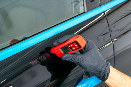 Male hand holds device for measuring coating thickness before polishing car. Measuring thickness of the car paint coating with paint thickness gauge. Polish car concept