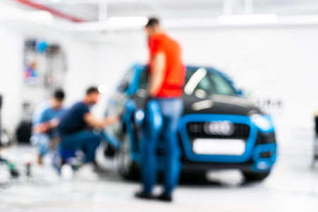 Blurred abstract image of man worker with car in a body shop. Blur car auto service. Car bokeh. Blurred background with car in garage. Vehicle maintenance in auto repair service. Blurry service station