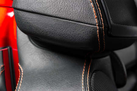 Modern luxury car black leather interior. Part of leather car seat details with red stitching. Interior of prestige modern car. Comfortable perforated leather seats. Black perforated leather. Car detailing
