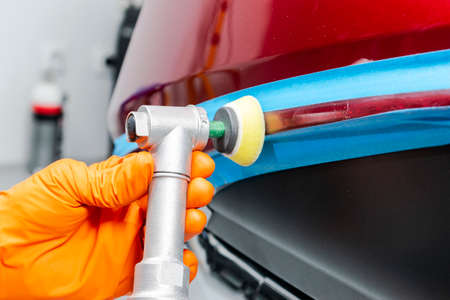 Car polish wax worker hands applying protective tape before polishing. Buffing and polishing car. Car detailing. Man holds a polisher in the hand and polishes the car 版權商用圖片 - 110778974