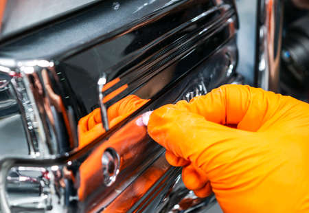 Car polish wax worker hands applying protective tape before polishing. Buffing and polishing car. Car detailing. Man holds a polisher in the hand and polishes the chrome car part
