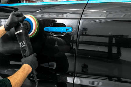 Car polish wax worker hands applying protective tape before polishing. Buffing and polishing car. Car detailing. Man holds a polisher in the hand and polishes the car Stock Photo