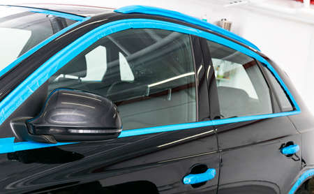 Car in applying blue protective tape before polishing. Buffing and polishing car. Car detailing. Car service Stock Photo
