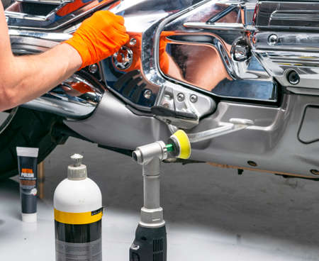 Car polish wax worker hands applying protective tape before polishing. Buffing and polishing motorcycle. Car detailing. Man holds a polisher in the hand and polishes the motorcycle