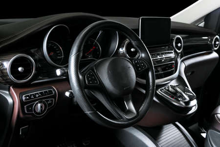 Modern Luxury car inside. Interior of prestige car. Comfortable leather seats. Brown perforated leather cockpit with white stitching. Steering wheel and dashboard. Automatic gear stick shift. Car detailing