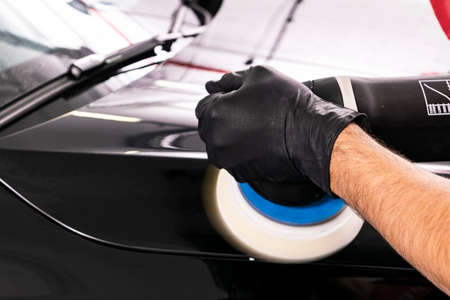 Car polish wax worker hands applying protective tape before polishing. Buffing and polishing car. Car detailing. Man holds a polisher in the hand and polishes the car Imagens