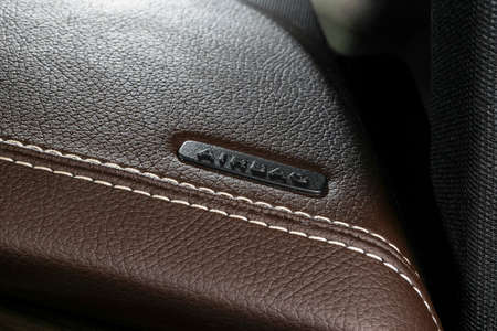 Modern sport car brown leather interior. Part of leather car cockpit details with stitching. Car detailing. Brown perforated leather cockpit with airbag Фото со стока