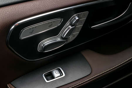 Door handle with Power window and seat control buttons of a luxury passenger car. Brown perforated leather interior with white stitching of the luxury modern car. Modern car interior details. Car detailing 免版税图像