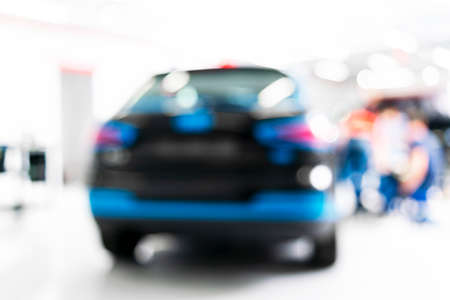 Blurred abstract image of man worker with car in body shop. Blur car auto service. Car bokeh. Blurred background with car in garage. Vehicle maintenance in auto repair service. Blurry service station