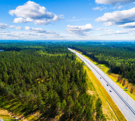 Aerial view of a country road in the forest with moving cars. Landscape. Captured from above with a drone. Aerial bird's eye road with car. Aerial top view forest. Texture of forest view from above. Standard-Bild