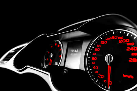 Close up shot of a speedometer in a car. Car dashboard. Dashboard details with indication lamps.Car instrument panel. Dashboard with speedometer, tachometer, odometer. Car detailing. Modern interior. Black and white