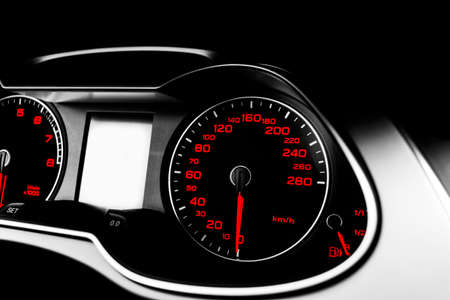 Close up shot of a speedometer in a car. Car dashboard. Dashboard details with indication lamps.Car instrument panel. Dashboard with speedometer, tachometer, odometer. Car detailing. Black and white Фото со стока