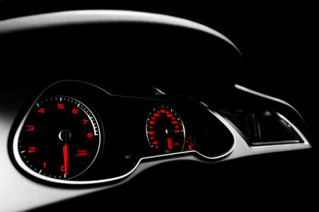 Close up shot of a speedometer in a car. Car dashboard. Dashboard details with indication lamps.Car instrument panel. Dashboard with speedometer, tachometer, odometer. Car detailing. Black and white Stock Photo
