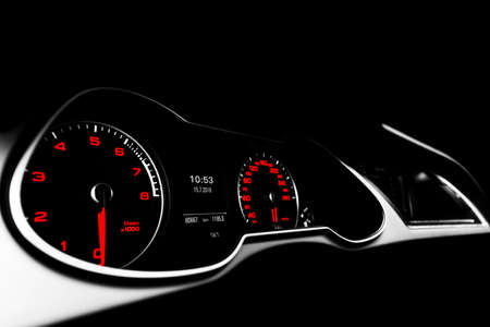 Close up shot of a speedometer in a car. Car dashboard. Dashboard details with indication lamps.Car instrument panel. Dashboard with speedometer, tachometer, odometer. Car detailing. Black and white Imagens