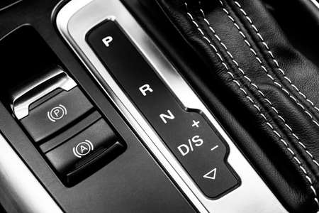 Automatic gear stick of a modern car. Maodern car interior details. Close up view. Car detailing. Automatic transmission lever shift. Black leather interior with red stitching. Black and white