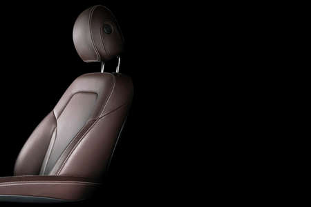 Modern luxury car brown leather interior. Part of leather car seat details with white stitching. Interior of prestige car. Comfortable perforated leather seats. Brown perforated leather. Car detailing