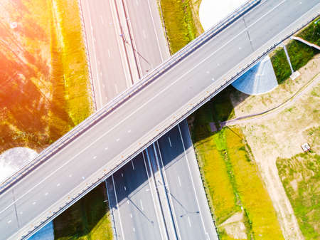 Aerial view of highway in city. Cars crossing interchange overpass. Highway interchange with traffic. Aerial birds eye photo of highway. Expressway. Road junctions. Car passing. Top view from above.