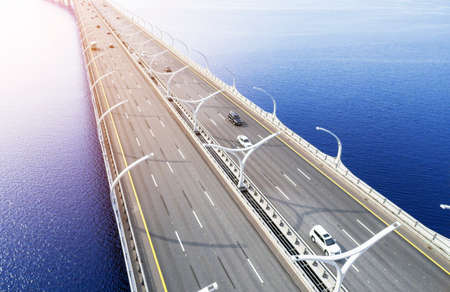 Aerial view of highway in the ocean. Cars crossing bridre interchange overpass. Highway interchange with traffic. Aerial birds eye photo of highway. Expressway. Road junctions. Car passing. Bridge with traffic
