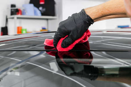 A man cleaning car with microfiber cloth. Car detailing concept. Car detailing. Cleaning with sponge. Car Worker cleaning with Microfiber. Solution to clean. Vehicle washing station