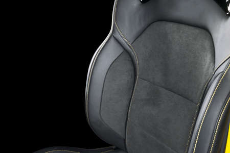 Black leather interior of the luxury modern car. Perforated Leather comfortable seats with yellow stitching isolated on black background. Modern car interior details. Car detailing
