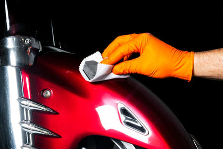 Car polish wax worker hands polishing motorcycle. Buffing and polishing vehicle with ceramic. Car detailing. Man holds a polisher in the hand and polishes the motorcycle with nano ceramic. Tools for polishing Stok Fotoğraf