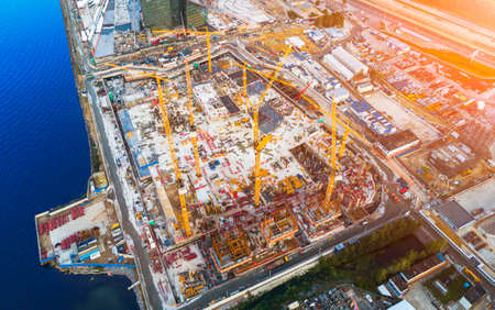 Aerial view of a Construction crane tower. Top view Crane and building working progress. Worker. Construction Site view by drone. Aerial top view a New buildings with a crane. Tower crane Stock Photo