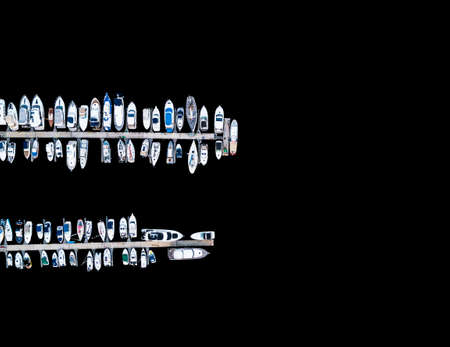 Aerial View by Drone of Yacht Club and Marina. Top view of yacht club. White boats in sea water. Marina dock yachts and small motor boats. Yacht and sailboat is moored at the quay. Parking Stock Photo