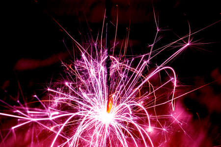 Burning christmas sparklers with long exposure. Beautiful sparkler firework flame on black background. Blurred lights of firework.  Burning sparkler with bright sparks in dusk. Stock Photo