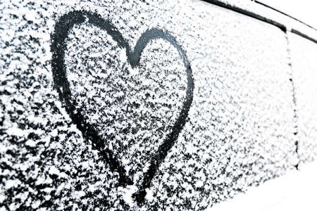 Heart symbol on frozen window of the car. Shape of heart drawn on snow on front window of the car. Heart snow. Christmas decorations and accessories Stock Photo