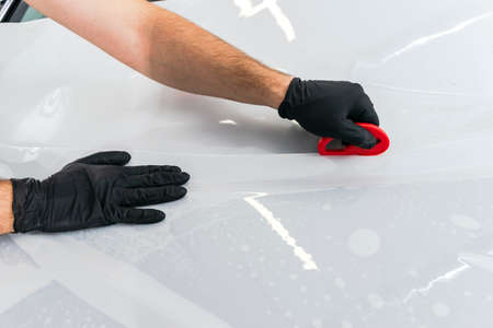 Car wrapping specialist putting vinyl foil or film on car. Protective film on the car. Applying a protective film to the car with tools for work. Car detailing. Transparent film. Car paint protection. Trimming.