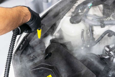 Car detailing. Car washing cleaning engine. Cleaning car engine using hot steam. Hot steam engine washing. Soft lighting. Car wash station worker cleaning vehicle. Car wash concept Stock Photo