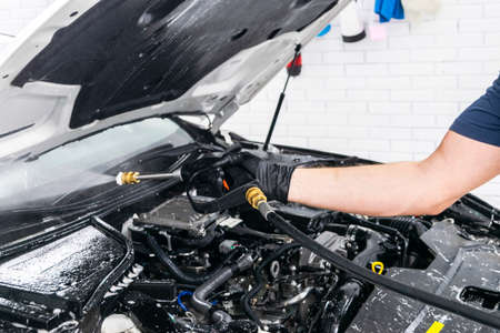 Car detailing. Manual car wash engine with pressure water. Washing car engine with water nozzle. Car washman worker cleaning vehicle engine. Man spraying pressure washer for car wash.