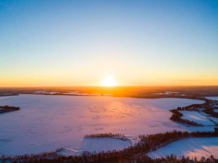 Aerial view of a gold sunset over winter snow-covered pine forest. Winter forest texture. Aerial view. Aerial drone view of a winter landscape. Snow covered forest. Dramatic gold sunset sky over frozen lake Stock Photo