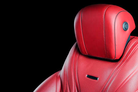 Red leather interior of the luxury modern car. Perforated red leather comfortable seats with stitching isolated on black background. Modern car interior details. Car detailing. Car inside