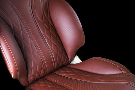 Brown leather interior of the luxury modern car. Perforated Leather comfortable red seats with stitching isolated on black background. Modern car interior details. Car detailing Stock Photo