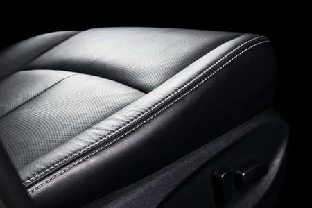 Black leather interior of the luxury modern car. Perforated Leather comfortable seats isolated on black background. Modern car interior details. Car detailing. Car inside