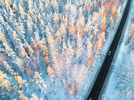 Aerial view of a car on winter road in the forest. Winter landscape countryside. Aerial photography of snowy forest with a car on the road. Captured from above with a drone. Aerial photo. Car in motion 스톡 콘텐츠 - 115051164