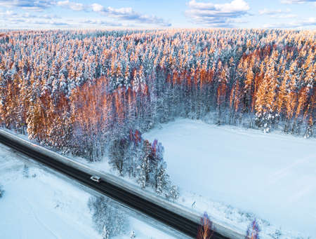 Aerial view of a car on winter road in the forest. Winter landscape countryside. Aerial photography of snowy forest with a car on the road. Captured from above with a drone. Aerial photo. Car in motion