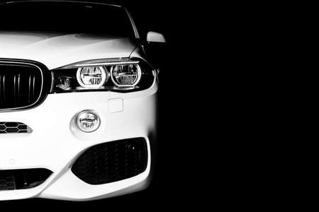 Headlight of a modern white sport car. The front lights of the car. Modern Car exterior details. Car detailing. Isolated on black background. Car detailing. Front view