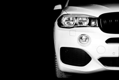 Headlight of a modern white sport car. The front lights of the car. Modern Car exterior details. Car detailing. Isolated on black background. Car detailing Standard-Bild